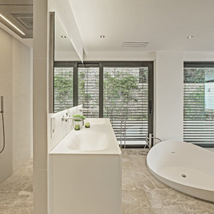 Modelo de cuarto de baño principal, contemporáneo, extra grande, con armarios con paneles lisos, puertas de armario blancas, bañera exenta, ducha abierta, paredes blancas, lavabo integrado y ducha abierta