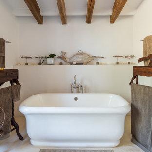 Diseño de cuarto de baño mediterráneo con bañera exenta, paredes blancas y suelo beige