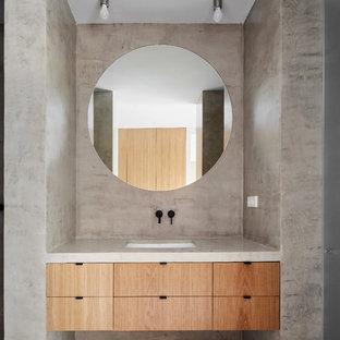 Modelo de cuarto de baño actual con armarios con paneles empotrados, puertas de armario de madera oscura, paredes grises, lavabo integrado y suelo gris