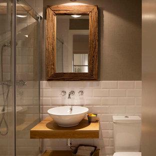 Foto de cuarto de baño con ducha, rústico, de tamaño medio, con armarios abiertos, puertas de armario de madera oscura, ducha empotrada, sanitario de dos piezas, baldosas y/o azulejos blancos, baldosas y/o azulejos de cerámica, paredes beige, lavabo sobreencimera, encimera de madera y encimeras marrones