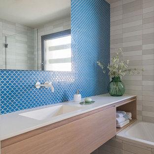 Ejemplo de cuarto de baño infantil, único y flotante, mediterráneo, de tamaño medio, con puertas de armario de madera clara, bañera empotrada, baldosas y/o azulejos azules, suelo de madera clara, encimeras blancas, armarios con paneles lisos, baldosas y/o azulejos en mosaico, lavabo integrado y suelo beige