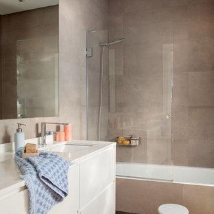 Modelo de cuarto de baño actual con armarios con paneles lisos, puertas de armario beige, bañera encastrada, combinación de ducha y bañera, baldosas y/o azulejos marrones, paredes marrones, lavabo bajoencimera, suelo marrón y encimeras beige