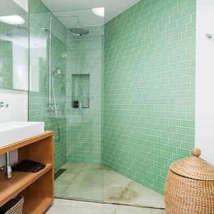 Foto de cuarto de baño contemporáneo con armarios abiertos, puertas de armario de madera oscura, ducha esquinera, baldosas y/o azulejos verdes, paredes blancas, suelo de cemento, lavabo sobreencimera, encimera de madera, suelo gris, ducha abierta y encimeras beige