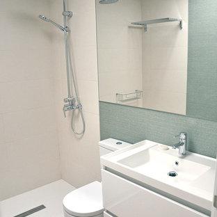 Idéer för små funkis en-suite badrum, med släta luckor, vita skåp, bambugolv, ett väggmonterat handfat, bänkskiva i akrylsten och dusch med skjutdörr