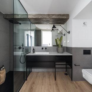 Diseño de cuarto de baño con ducha, actual, con armarios tipo mueble, puertas de armario negras, ducha a ras de suelo, baldosas y/o azulejos grises, paredes blancas, lavabo integrado, suelo beige, ducha abierta y encimeras blancas