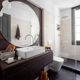 Imagen de cuarto de baño con ducha, actual, de tamaño medio, con armarios con paneles lisos, puertas de armario de madera en tonos medios, ducha empotrada, sanitario de pared, baldosas y/o azulejos beige, baldosas y/o azulejos de porcelana, paredes blancas, lavabo sobreencimera, encimera de madera, suelo gris y encimeras marrones