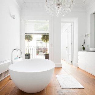 Foto de cuarto de baño principal, tradicional renovado, grande, con armarios con paneles lisos, puertas de armario blancas, bañera exenta, paredes blancas, suelo de madera en tonos medios, lavabo sobreencimera y encimera de granito