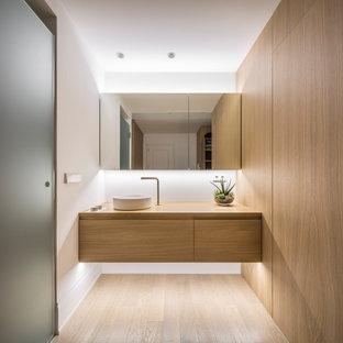Modern inredning av ett mellanstort badrum, med vita väggar, ett fristående handfat, träbänkskiva, beiget golv, släta luckor, skåp i ljust trä och ljust trägolv