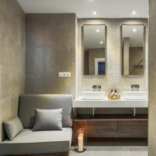 Modelo de cuarto de baño principal, bohemio, con armarios con paneles lisos, puertas de armario de madera en tonos medios, baldosas y/o azulejos beige, paredes beige, suelo de azulejos de cemento, lavabo sobreencimera, suelo beige y encimeras blancas