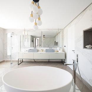 Modelo de cuarto de baño principal, contemporáneo, con armarios con paneles lisos, puertas de armario blancas, bañera exenta, ducha a ras de suelo, lavabo sobreencimera y ducha con puerta con bisagras