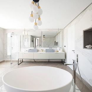 Imagen de cuarto de baño principal, contemporáneo, extra grande, con armarios con paneles lisos, puertas de armario blancas, bañera exenta, ducha a ras de suelo, paredes blancas, lavabo sobreencimera y ducha con puerta con bisagras