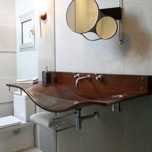 Modelo de cuarto de baño con ducha, contemporáneo, de tamaño medio, con sanitario de una pieza, baldosas y/o azulejos grises, baldosas y/o azulejos de porcelana, suelo de baldosas de porcelana, lavabo integrado, encimera de madera, suelo gris y encimeras marrones