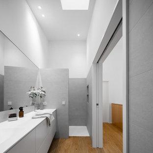 Diseño de cuarto de baño minimalista con armarios con paneles lisos, puertas de armario grises, ducha a ras de suelo, paredes blancas, suelo de madera en tonos medios, lavabo integrado, suelo marrón, ducha abierta y encimeras blancas