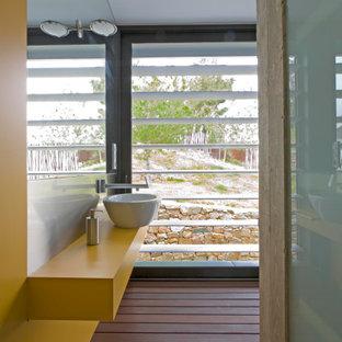 Ejemplo de cuarto de baño con ducha, actual, de tamaño medio, con puertas de armario amarillas, paredes amarillas, lavabo sobreencimera, suelo marrón y encimeras amarillas