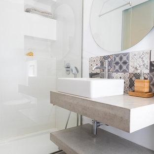 Bild på ett funkis badrum med dusch, med öppna hyllor, en kantlös dusch, grå kakel, vita väggar, bänkskiva i betong och grått golv