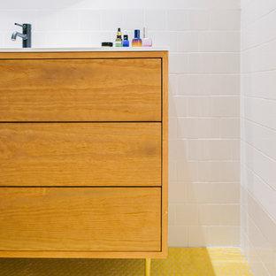 Idee per una stanza da bagno padronale minimalista con consolle stile comò, ante bianche, vasca freestanding, doccia alcova, WC sospeso, piastrelle bianche, piastrelle di vetro, pareti bianche, pavimento con piastrelle a mosaico, top in superficie solida, pavimento giallo, porta doccia scorrevole e top bianco