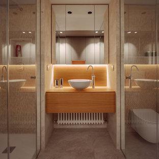 Стильный дизайн: ванная комната среднего размера в современном стиле с плоскими фасадами, фасадами цвета дерева среднего тона, душем в нише, бежевой плиткой, керамогранитной плиткой, полом из керамогранита, душевой кабиной, настольной раковиной, столешницей из дерева, бежевым полом, душем с распашными дверями, бежевой столешницей, тумбой под одну раковину, подвесной тумбой и унитазом - последний тренд