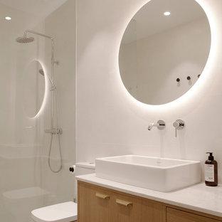 Diseño de cuarto de baño con ducha, escandinavo, con ducha a ras de suelo, lavabo sobreencimera, armarios con paneles lisos, puertas de armario de madera clara, sanitario de una pieza, paredes blancas, suelo beige, ducha abierta y encimeras blancas