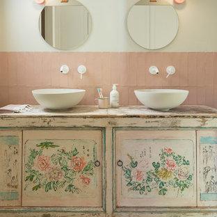Imagen de cuarto de baño infantil, romántico, de tamaño medio, con armarios tipo mueble, suelo de madera en tonos medios, lavabo sobreencimera, encimera de madera, puertas de armario con efecto envejecido, baldosas y/o azulejos rosa y paredes beige