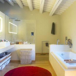 Diseño de cuarto de baño principal, mediterráneo, de tamaño medio, con bañera encastrada, ducha esquinera, paredes amarillas, suelo de madera en tonos medios, lavabo sobreencimera y encimera de cemento
