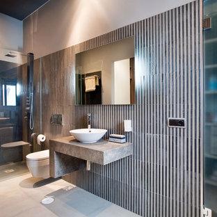 Diseño de cuarto de baño con ducha, contemporáneo, con ducha a ras de suelo, lavabo sobreencimera, sanitario de pared, baldosas y/o azulejos blancas y negros, paredes grises, suelo gris, ducha abierta y encimeras grises