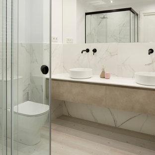 Ejemplo de cuarto de baño contemporáneo con armarios con paneles lisos, puertas de armario beige, ducha esquinera, sanitario de dos piezas, baldosas y/o azulejos blancos, paredes blancas, suelo de madera clara, lavabo sobreencimera, suelo beige y encimeras blancas
