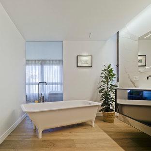 Diseño de cuarto de baño principal, actual, con bañera con patas, baldosas y/o azulejos blancos, baldosas y/o azulejos de mármol, paredes blancas, armarios con paneles lisos, suelo de madera en tonos medios, lavabo tipo consola y suelo marrón