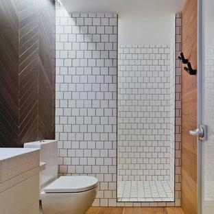 Imagen de cuarto de baño principal, contemporáneo, con armarios con paneles lisos, bañera con patas, baldosas y/o azulejos blancos, baldosas y/o azulejos de mármol y paredes blancas