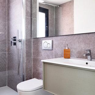 Foto de cuarto de baño con ducha, contemporáneo, con armarios con paneles lisos, puertas de armario grises, ducha esquinera, sanitario de pared, lavabo integrado, suelo marrón y encimeras blancas