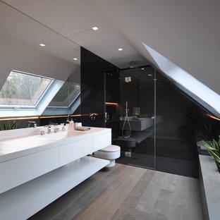 Réalisation d'une salle de bain design de taille moyenne avec un placard à porte plane, des portes de placard blanches, un WC suspendu, un mur blanc, un lavabo intégré, un plan de toilette en surface solide et un sol en bois brun.