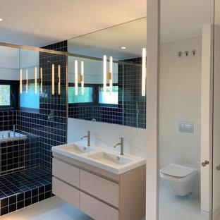 Idee per una grande stanza da bagno padronale design con ante lisce, ante in legno chiaro, vasca giapponese, vasca/doccia, WC monopezzo, piastrelle blu, piastrelle in ceramica, lavabo sospeso, pavimento bianco, porta doccia scorrevole e top bianco