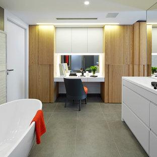 Modelo de cuarto de baño principal, actual, con armarios con paneles lisos, puertas de armario blancas, bañera exenta y suelo de baldosas de cerámica