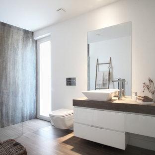 Ejemplo de cuarto de baño con ducha, contemporáneo, de tamaño medio, con armarios con paneles lisos, puertas de armario blancas, sanitario de pared, paredes blancas, lavabo sobreencimera, suelo marrón y encimeras marrones