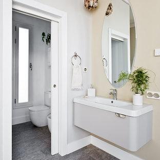 Modelo de cuarto de baño bohemio con lavabo integrado, suelo gris y encimeras blancas