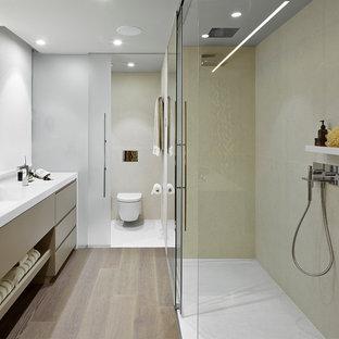 Ispirazione per una stanza da bagno con doccia contemporanea di medie dimensioni con ante lisce, doccia a filo pavimento, WC sospeso, lavabo integrato, ante in legno chiaro, piastrelle beige, parquet chiaro e porta doccia scorrevole