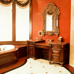 На фото: с высоким бюджетом огромные главные ванные комнаты в классическом стиле с ванной в нише, фасадами с выступающей филенкой, фасадами цвета дерева среднего тона, душем в нише, оранжевыми стенами, полом из линолеума, столешницей из дерева, разноцветным полом, душем с распашными дверями и коричневой столешницей