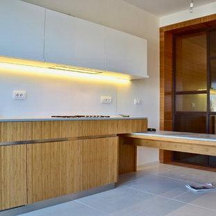 ローマの大きいコンテンポラリースタイルのおしゃれなキッチン (ドロップインシンク、フラットパネル扉のキャビネット、白いキャビネット、コンクリートカウンター、白いキッチンパネル、ガラス板のキッチンパネル、シルバーの調理設備の、コンクリートの床、白い床) の写真