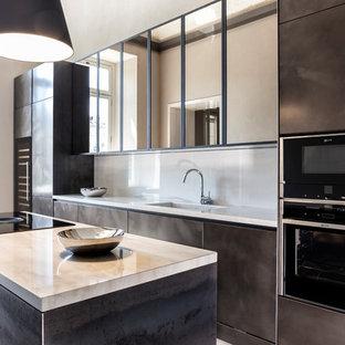Idee per una cucina parallela design con lavello integrato, ante marroni, paraspruzzi beige, elettrodomestici neri, isola e top beige