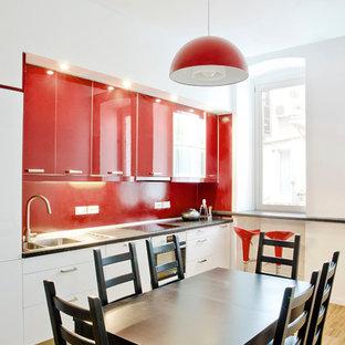 Einzeilige, Mittelgroße Moderne Wohnküche mit Einbauwaschbecken, flächenbündigen Schrankfronten, roten Schränken, Küchenrückwand in Rot, weißen Elektrogeräten und hellem Holzboden in Sonstige