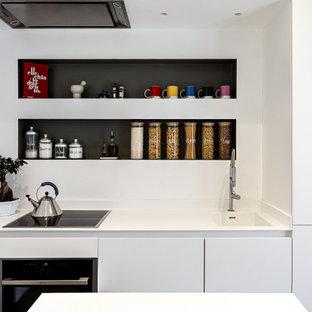 Ispirazione per una piccola cucina minimal con lavello integrato, ante lisce, ante bianche, top in superficie solida, paraspruzzi bianco, elettrodomestici da incasso, pavimento in gres porcellanato, penisola, pavimento grigio e top bianco
