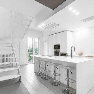 Esempio di una cucina parallela minimal con ante lisce, ante bianche, elettrodomestici in acciaio inossidabile, isola, pavimento grigio e top bianco