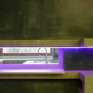 ローマの中サイズのモダンスタイルのおしゃれなキッチン (ドロップインシンク、フラットパネル扉のキャビネット、濃色木目調キャビネット、コンクリートカウンター、シルバーの調理設備の、クッションフロア、緑の床) の写真