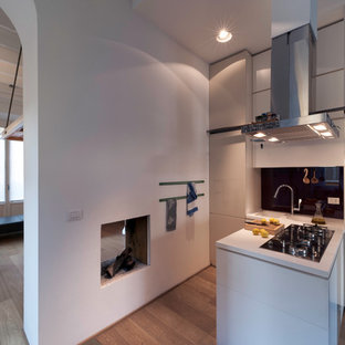 Mid-sized contemporary l-shaped eat-in kitchen in Milan with an integrated sink, flat-panel cabinets, white cabinets, solid surface benchtops, red splashback, glass sheet splashback, stainless steel appliances, light hardwood floors, a peninsula and beige floor.
