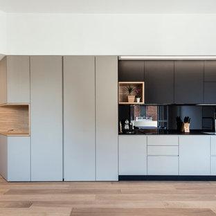 ミラノの中サイズのコンテンポラリースタイルのおしゃれなキッチン (ダブルシンク、フラットパネル扉のキャビネット、黒いキャビネット、ラミネートカウンター、黒いキッチンパネル、ガラス板のキッチンパネル、シルバーの調理設備の、淡色無垢フローリング、アイランドなし) の写真