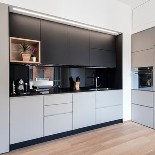 Inspiration for a mid-sized contemporary l-shaped kitchen in Milan with a double-bowl sink, flat-panel cabinets, laminate benchtops, black splashback, glass sheet splashback, stainless steel appliances, light hardwood floors, no island and grey cabinets.