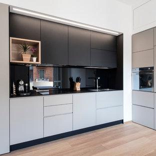 Immagine di una cucina a L design di medie dimensioni con lavello a doppia vasca, ante lisce, top in laminato, paraspruzzi nero, paraspruzzi con lastra di vetro, elettrodomestici in acciaio inossidabile, parquet chiaro, nessuna isola e ante grigie