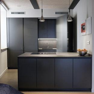 Esempio di una cucina design di medie dimensioni con top in laminato, parquet chiaro, pavimento beige, lavello sottopiano, ante lisce, ante nere, paraspruzzi grigio, elettrodomestici da incasso, penisola e top nero