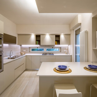 This is an example of a large modern separate kitchen in Other with a double-bowl sink, flat-panel cabinets, beige cabinets, beige splashback, stainless steel appliances, light hardwood floors and a peninsula.
