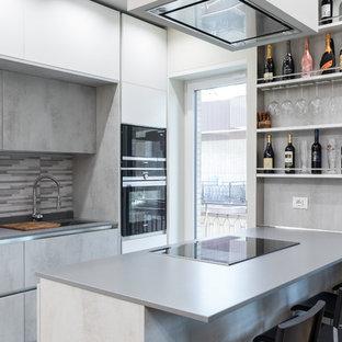 Idee per una cucina a corridoio contemporanea con lavello sottopiano, ante lisce, ante grigie, paraspruzzi grigio, elettrodomestici neri e top grigio