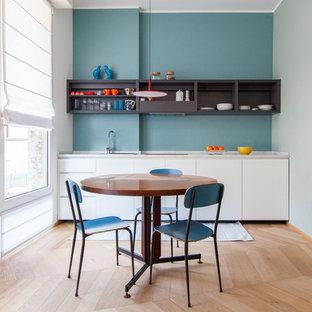 Inredning av ett modernt litet linjärt kök och matrum, med en nedsänkt diskho, släta luckor, vita skåp, mellanmörkt trägolv, beiget golv, granitbänkskiva, blått stänkskydd och integrerade vitvaror